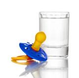 Baby dummy with alcoholic beverage isolated on white