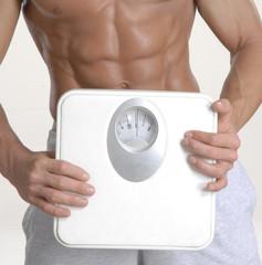 Hombre en forma cuidando su peso,balanza de peso.