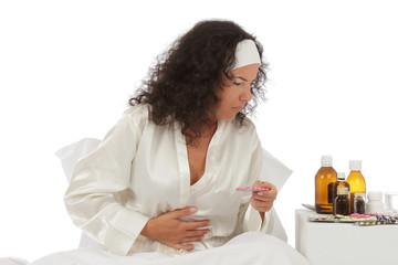 femme malade au lit avec médicaments