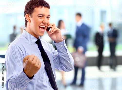 Portrait of happy businessman talking on mobile