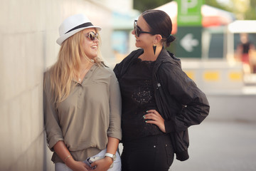 Two fashion woman standing outdoor and smiling