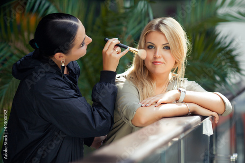 Makeup master doing visage to young beautiful model