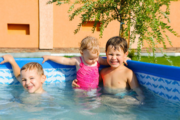 Two brothers and baby sister in the pool