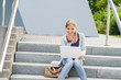 Young student woman sitting on university steps