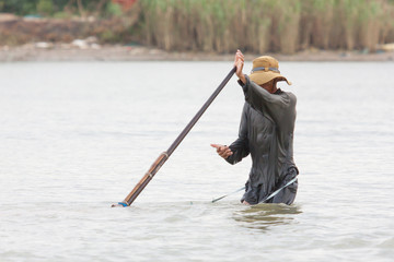 A vietnamese fisherman is searching for snakes and shells in the