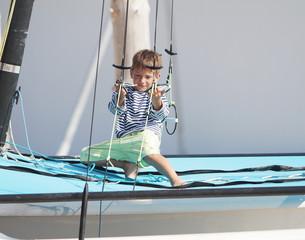 young cute child boy on sea catamaran / yacht
