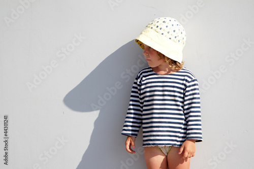 young girl standing next to grey wall and making shadow