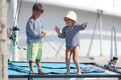 two cute children in sailor t-shirt on sea catamaran / yacht
