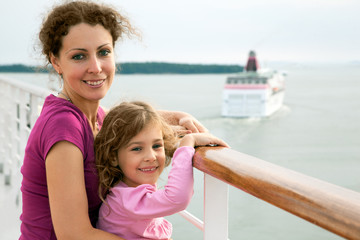 smiling mother and daughter traveling on big cruise ship