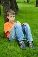 Boy in orange t-shirt sits with thoughtful face on grass