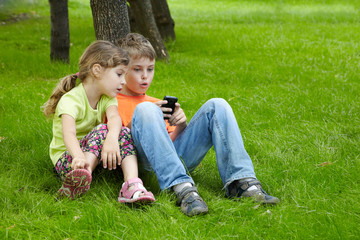 Boy and his younger sister sit on grass under tree in park