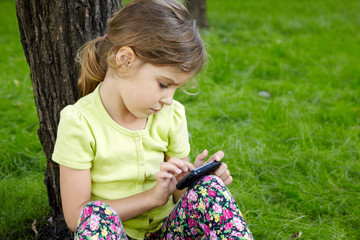 Girl sits leaning on tree in park and plays with cell phone