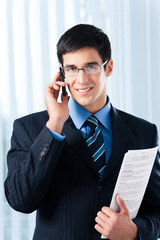 Businessman with cellphone and documents