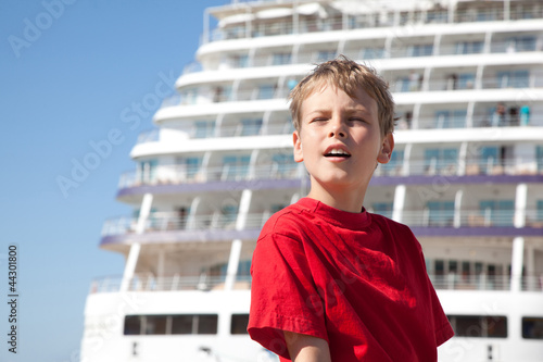 little boy closed eyes against background ship