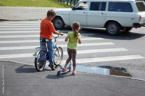 Boy with bicycle and his younger sister with scooter stand