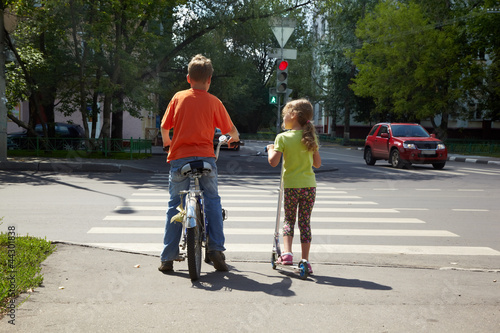 Boy with bicycle and his younger sister with scooter