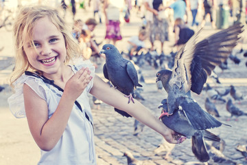 Smiling girl with pigeons on the arm