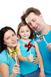 Mother, father and little daughter stand with colorful windmills