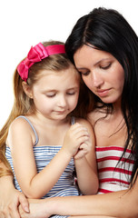 Mother and daughter in striped sundresses pray close-up