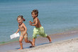 outdoor portrait of two children running on beach on sea backgro