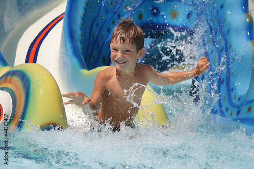 outdoor portrait of young smiling child having fun in aquapark