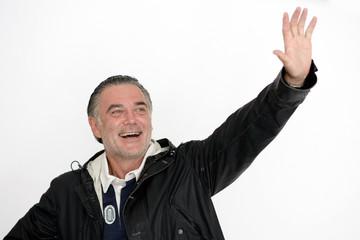 Mann in Regenjacke grüßt