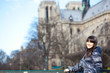 Happy beautiful brunette tourist in Paris near Notre-Dame de Par