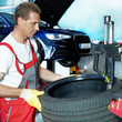 Car mechanic is fitting a summer tyre in front of a service lift