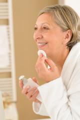 Senior woman in bathroom use cotton pad