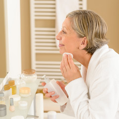 Senior woman apply face cleaning lotion