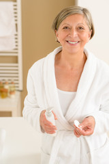 Senior woman in bathrobe hold cotton pad