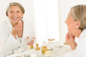 Senior woman smiling bathroom mirror reflection