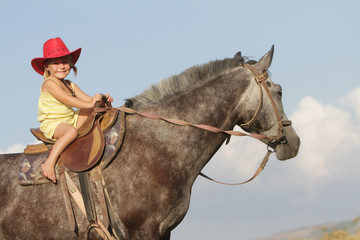 young happy girl in cowboy hat riding horse