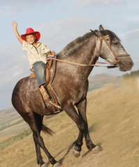 young happy boy in cowboy hat riding horse on natural background