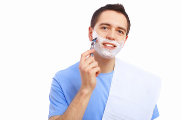 Young man at home shaving himself
