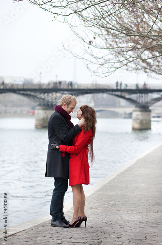 Romantic couple in love hugging near Pont des Arts in Paris at s