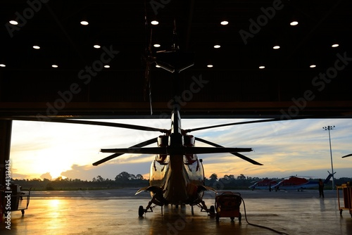 Tuinposter Helicopter silhouette of helicopter in the hangar
