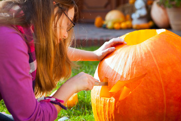 girl carving jack-o-lantern
