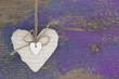 Ein Herz auf violetten Holzhintergrund