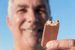 Mature man eating chocolate