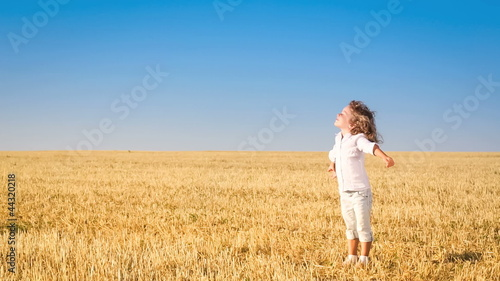 Happy child enjoying the nature in autumn field
