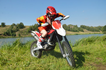 The girl sitting on a sport bike, amid lakes and forests.