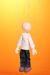 Wooden puppet on orange background