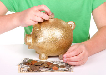 child putting money in piggy bank
