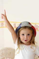 Cheerful girl wearing hat playing on the cradle
