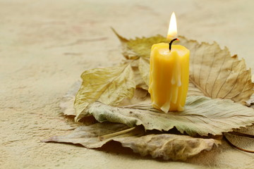 Yellow candle on the autumn leaves, autumn style