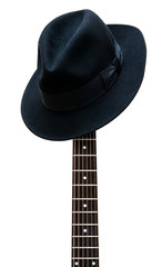 Vintage hat resting on a guitar fretboard isolated background