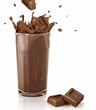 Chocolate cubes splashing into a choco milkshake glass. With two