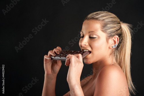 Beautiful woman with golden make up eating chocolate