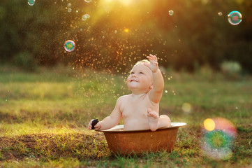 Baby splashing in a basin outdoors